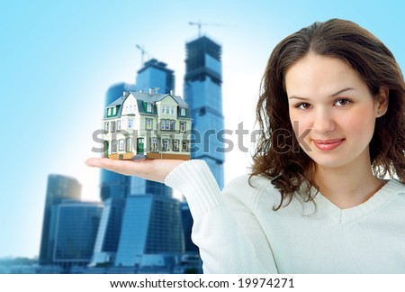 woman with little house on hand on business glass buildings
