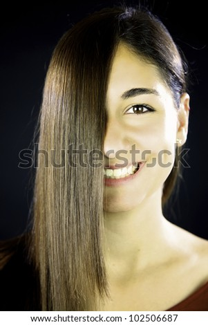 woman with long brunette straight hair in front of her face