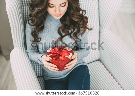 Woman with long curly hair holding and looking at a gift box heart. Valentine's Day. - stock photo
