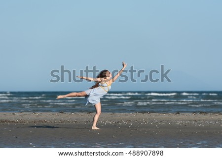 Woman with long curly hair wear dance dress and making moves, standing on the beach. Wind wave the skirt. Sea and sky as background