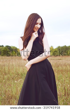 Woman with long dark hair and black feathers standing outdoors outdoors young witch look - stock photo