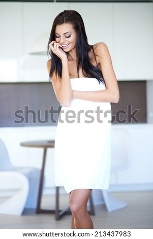 Woman with Long Dark Hair Wearing Bath Towel with Hand Touching Chin and Looking Down