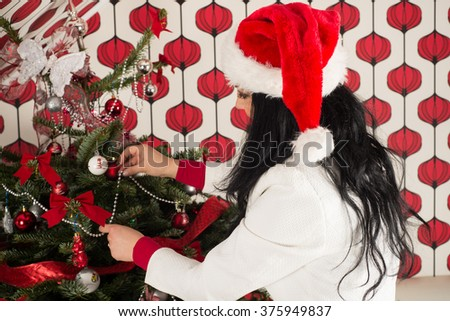 Woman with long hair and santa hat decorate natural Christmas tree
