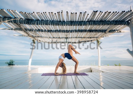 Woman with long hair and slim body make morning yoga exercise on the yoga mat on white wooden terrace. Yoga pose. Bridge pose.  - stock photo