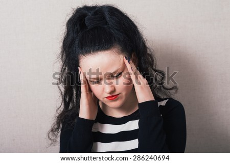 Woman with long hair put her hands on her head, headache. Gray background - stock photo