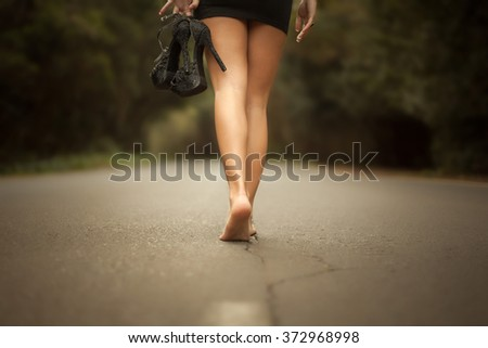 Woman with long legs walking barefoot on a road with shoes in hand