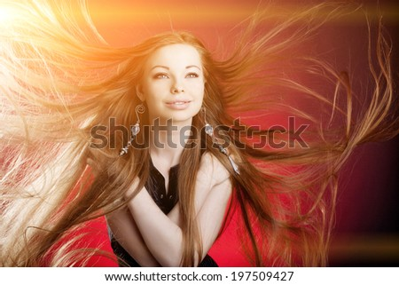 Woman with long luxury hair. Beautiful young stylish fashionable girl with flying hair in the wind