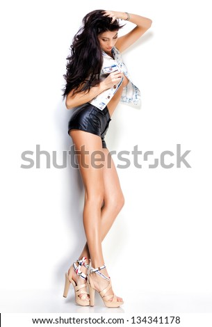 woman with long sexy legs wearing leather shorts and denim jacket on white background - stock photo