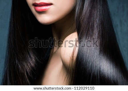woman with long shiny black hair and red lips studio shot - stock photo