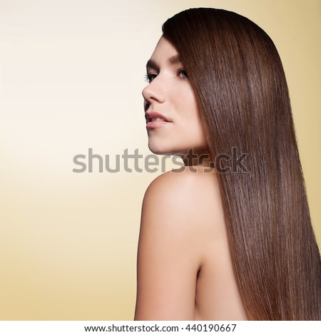 Woman with long thick straight hair on a gold background in profile