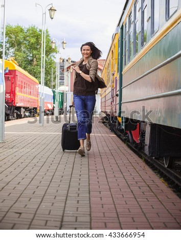 woman with luggage on the station platform runs  for passenger train along the railcar - stock photo