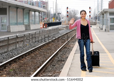 woman with luggage waving at train station - stock photo