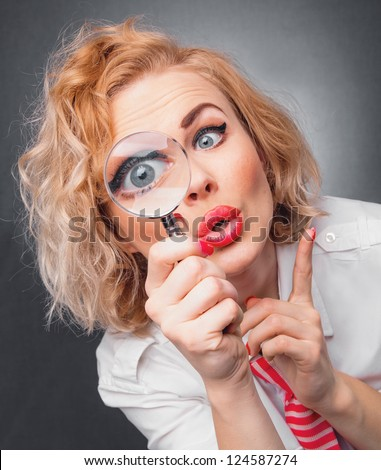 Woman with magnifier, close-up expressive face of a funny female