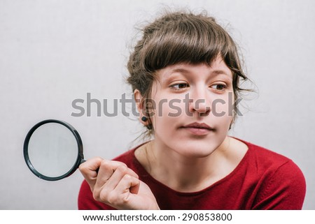 Woman with magnifying glass . On a gray background.