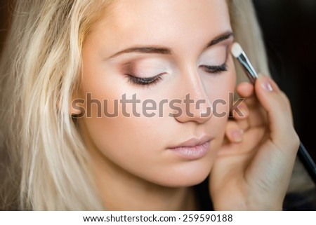 Woman with make up brush - stock photo