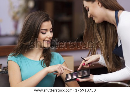Woman with makeup artist choosing color of eyeshadow - stock photo