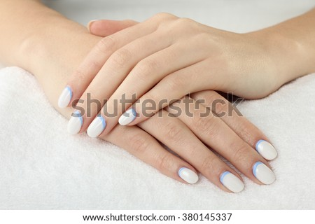 woman with manicure on white fluffy towel closeup