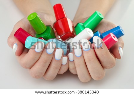 woman with manicure on white table. A lot of colorful nail Polish closeup