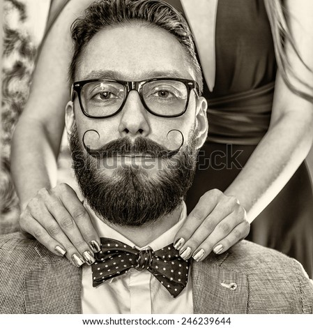 Woman with manicure straightens a bow tie to old-fashioned man in glasses with a beard and curled mustache. Photo toned in sepia, stylized retro shoot.