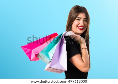 Woman with many shopping bags on blue background