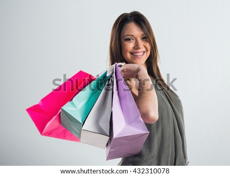 Woman with many shopping bags over grey background