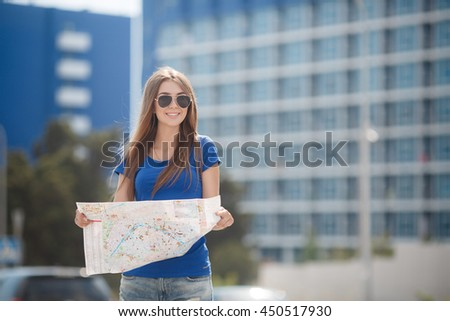 woman with map and suitcase in city street. traveler girl searching for her destination on the map. traveling adventures. voyage or trip - stock photo