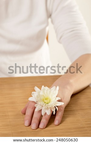 Woman with margarita flower on her hand in a nail salon