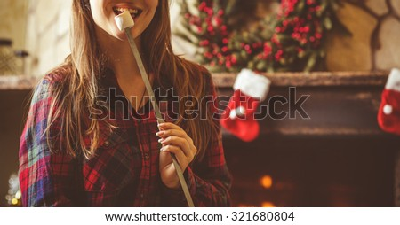 Woman with marshmallow by the fireplace. Young woman smiling and eating roasted marshmallow by the warm fireplace decorated for Christmas. Relaxed holiday evening concept. - stock photo
