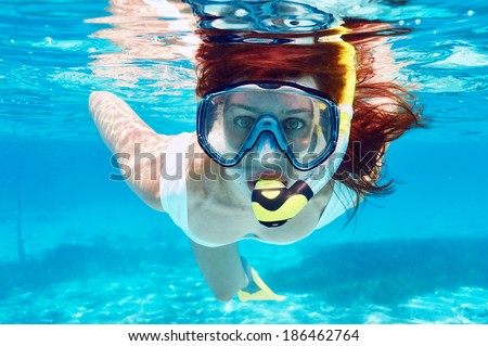 Woman with mask snorkeling in clear water  - stock photo