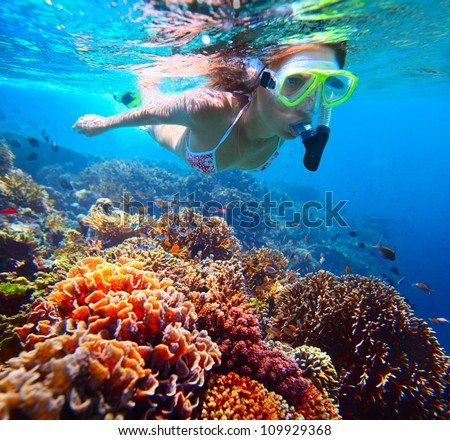 Woman with mask snorkeling in clear water over vivid coral reef - stock photo
