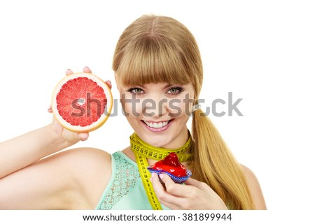 Woman with measuring tape holds in hands cake and grapefruit choosing, deciding between sweet food or fresh fruit, make dietary choice. Weight loss diet dilemma concept. Isolated on white