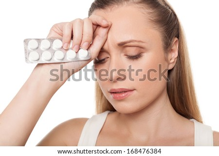 Woman with medicines. Depressed young woman holding medicines and touching head with hand while standing isolated on white - stock photo