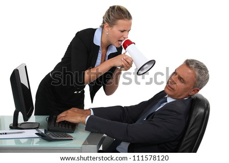 Woman with megaphone yelling at man in the office - stock photo