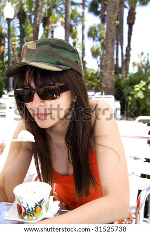 Woman with military hat and sun glasses eating ice cream