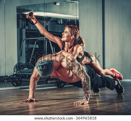 woman with mobile phone training with muscular handsome man bodybuilder in gym - stock photo