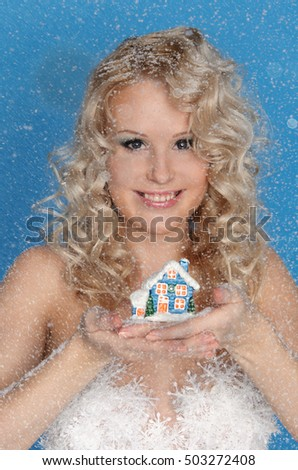 woman with model of house and snow on blue background
