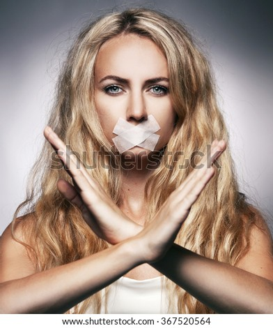 Woman with mouth sealed plaster. Fear, silence, violence - stock photo