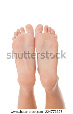 Woman with neat manicured natural nails without nail varnish showing her hands and bare feet in a beauty concept on a white background
