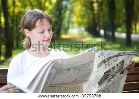 woman with newspaper in park - stock photo