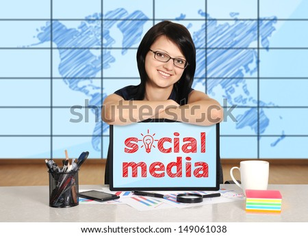 woman with note pad sitting in office, social media concept - stock photo