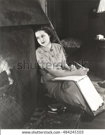 Woman with notebook daydreaming by fireplace