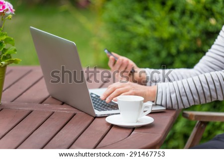 Woman with notebook on the garden, working outside.