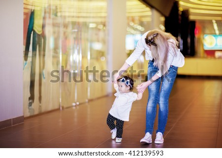 Woman with one year old child walking in supermarket and walking hold each other