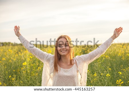 woman with open arms in the green rapeseed field at the morning