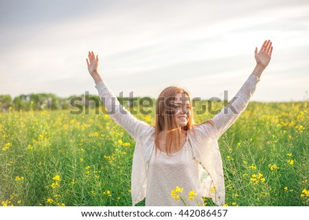 woman with open arms in the green wheat field at the morning.