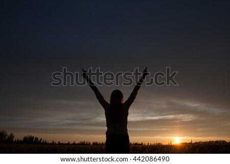 woman with open arms in the green wheat field at the morning
