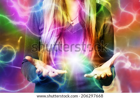 woman with open hands and colors flowing around, creativity concept - stock photo