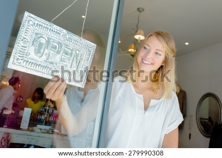 Woman with open shop sign - stock photo