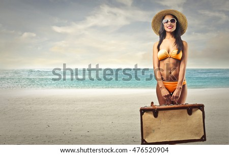 Woman with orange bikini holding a suitcase to go on vacation