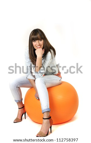 Woman with orange pilates ball concept shot.
